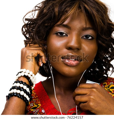 Smiling woman listening to music on a MP3 player isolated over white - stock photo
