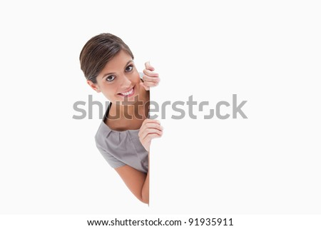 Smiling woman looking around the corner against a white background - stock photo
