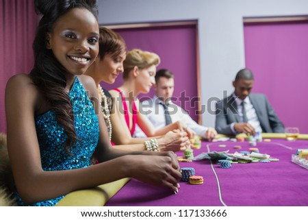 Smiling woman looking up from poker game in casino - stock photo