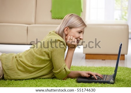 Smiling woman lying on floor at home looking at laptop screen, typing.? - stock photo