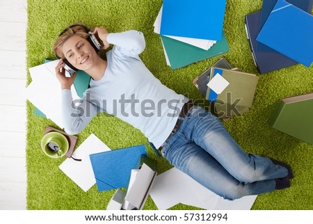 Smiling woman lying on floor listening to music with headset, surrounded with papers.?