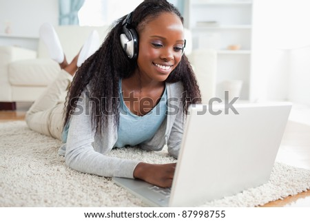 Smiling woman lying on floor with her notebook listening to music - stock photo