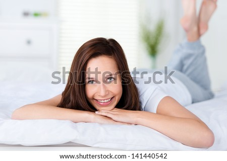 Smiling woman lying on her bed on her stomach facing the camera relaxing while enjoying a lazy day - stock photo
