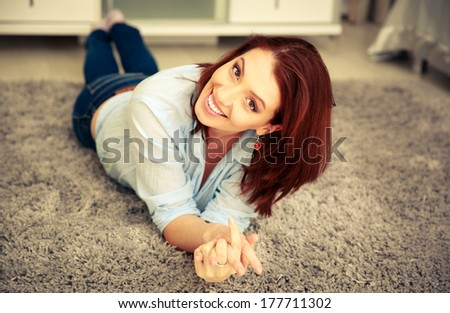 Smiling woman lying on the carpet at home - stock photo
