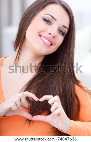 Smiling woman making heart sign - stock photo