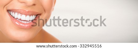 Smiling woman mouth with great teeth. Over gray background