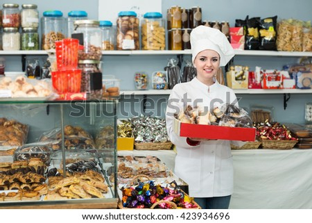 Smiling woman offering fresh and tasty pastry in bakery - stock photo