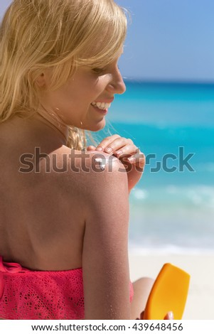 Smiling woman on beach vacation applying sunscreen protection on her skin, back view - stock photo