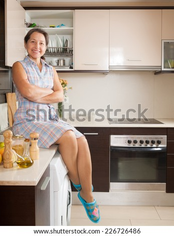 Smiling woman on table of domestic kitchen - stock photo