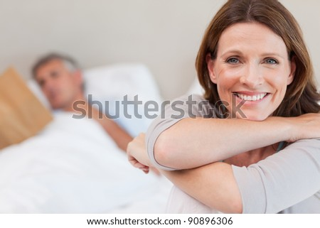 Smiling woman on the bed with reading husband in the background - stock photo