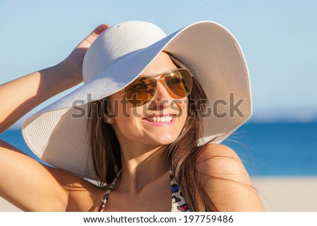 smiling woman on vacation with  sun hat and glasses.  - stock photo