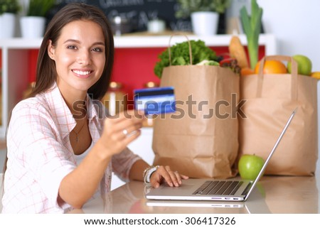 Smiling woman online shopping using tablet and credit card in kitchen . - stock photo