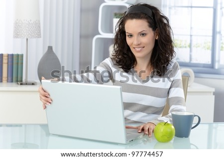 Smiling woman opening laptop computer at home, sitting by desk. - stock photo