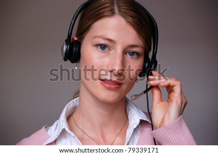 Smiling woman operator with headset - microphone and headphones - stock photo