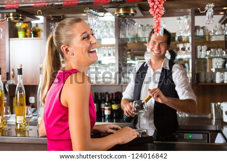 Smiling woman ordering a glass of wine at bar in Restaurant or Hotel