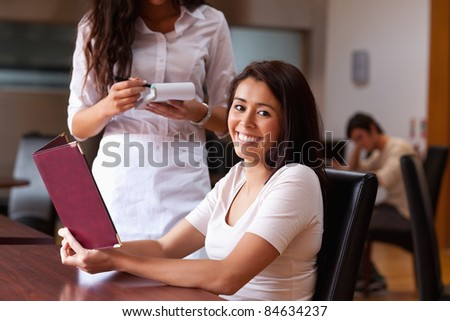 Smiling woman ordering a meal in a restaurant - stock photo