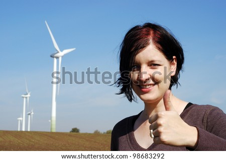 smiling woman outdoors in front of a wind park