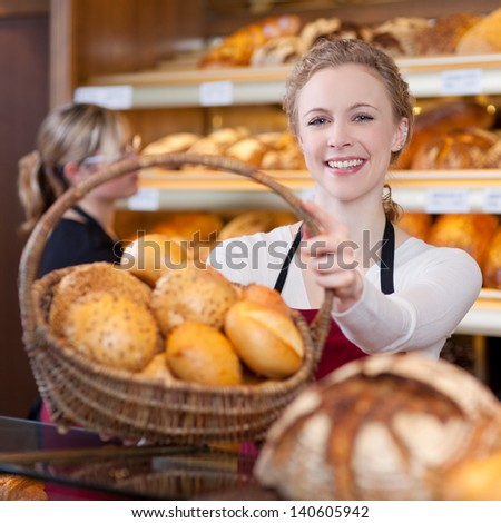 smiling woman passing basket of breads in bakery - stock photo