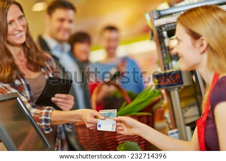 Smiling woman paying with Euro money bill at supermarket checkout - stock photo