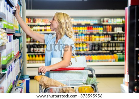 Smiling woman picking dairy products at supermarket - stock photo