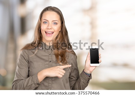 Smiling woman pointing on smartphone