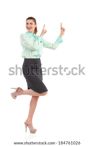 Smiling woman pointing up. Smiling attractive woman raising hands and pointing up. Full length studio shot isolated on white. - stock photo