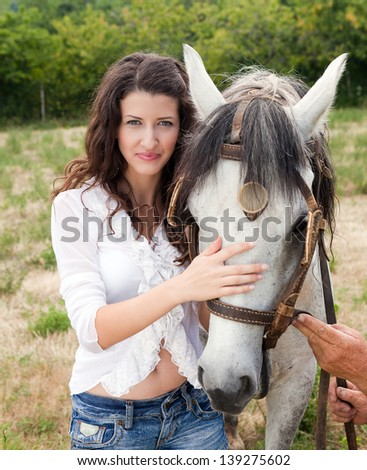 Smiling woman posing with her favorite farm horse - stock photo