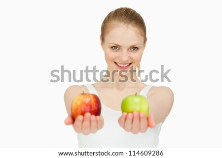 Smiling woman presenting two apples against white background