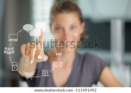 Smiling woman  pressing  touch screen on social network icon - stock photo
