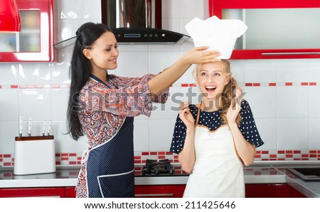 Smiling woman putting a chef hat on her younger friend's head - stock photo
