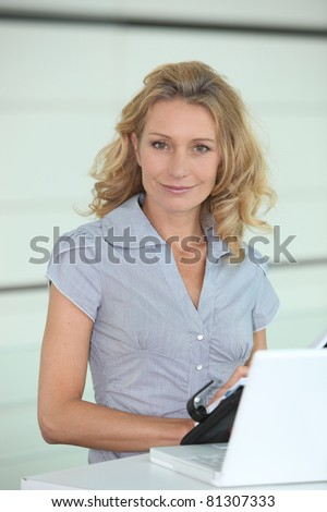 Smiling woman putting a date in her diary - stock photo