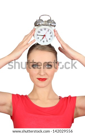Smiling woman  putting alarm clock on her head - stock photo