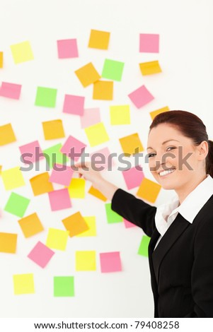 Smiling woman putting re-positionable notes on a white wall against a white background