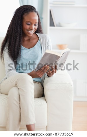 Smiling woman reading a book on her sofa