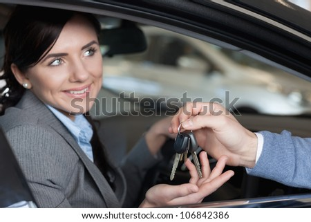 Smiling woman receiving keys from a man while sitting on a car