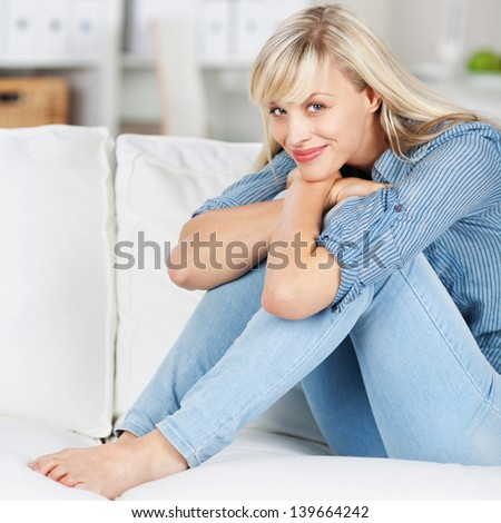 Smiling woman relaxing and embracing her legs