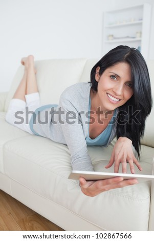 Smiling woman resting on a sofa while playing with a tablet in a living room - stock photo