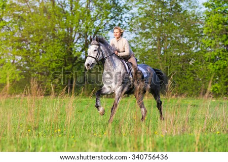 Smiling woman riding gallop on a horse in summer meadow.