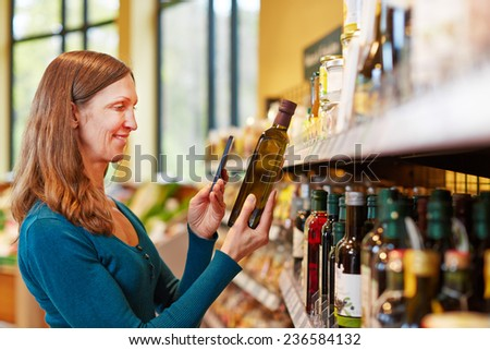 Smiling woman scanning a bottle of olive oil in a supermarket with her smartphone - stock photo