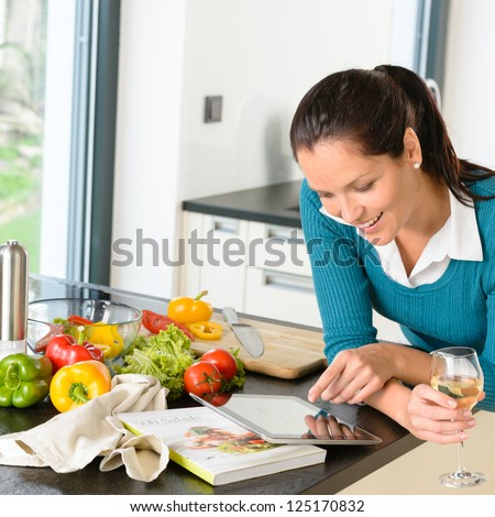 Smiling woman searching recipe tablet kitchen cooking food vegetables - stock photo
