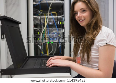 Smiling woman searching through servers in data center - stock photo