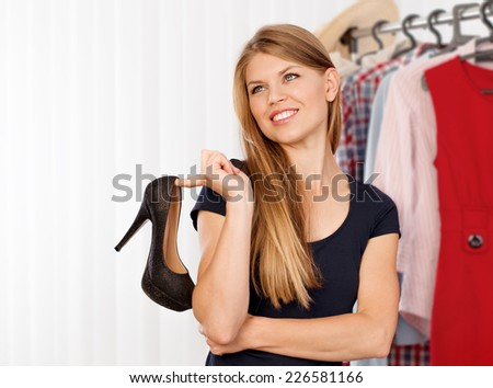 Smiling woman shopper choosing modern shoes in the store. Lovely Caucasian female model buying footwear in shopping mall. - stock photo