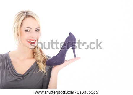 Smiling woman shopper or saleslady displaying a shoe on her outstretched palm isolated on white with lots of copyspace - stock photo