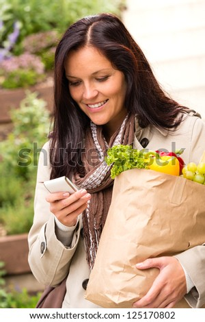 Smiling woman shopping vegetables mobile phone groceries messaging sms