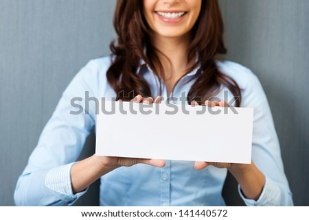 Smiling woman showing a white empty card in a close up shot - stock photo