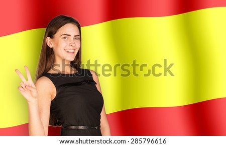 Smiling woman showing peace on Spain flag background
