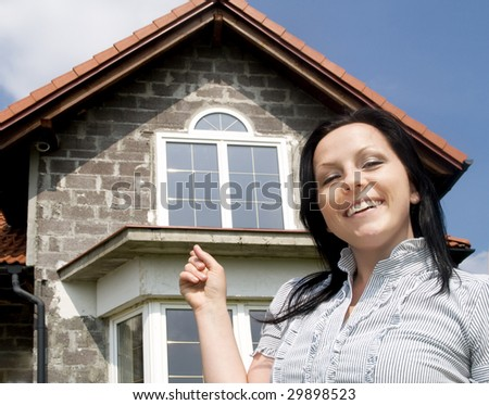 smiling woman showing the new house - stock photo