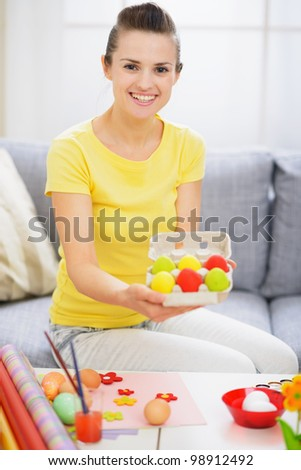 Smiling woman showing tray with colorful Easter eggs