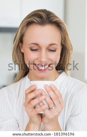 Smiling woman sitting and holding mug at home in the kitchen