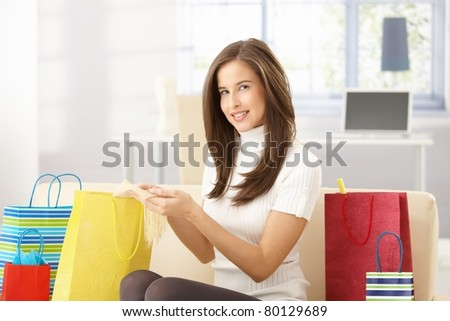 Smiling woman sitting at home with shopping bags, checking purchased goods, looking at camera.?